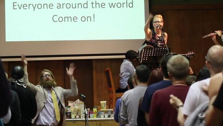 Een van The Sunday Assembly's diensten, met linksonder kerkleider Sanderson Jones. Fragment uit een YouTube-filmpje. Beeld The Sunday Assembly