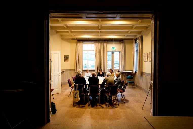 Aan zin om te discussiëren ontbreekt het de acht deelnemers, aan tafel met de organisator, niet. 'Het is fijn om mensen te ontmoeten die de diepte in willen.' Beeld Olaf Kraak