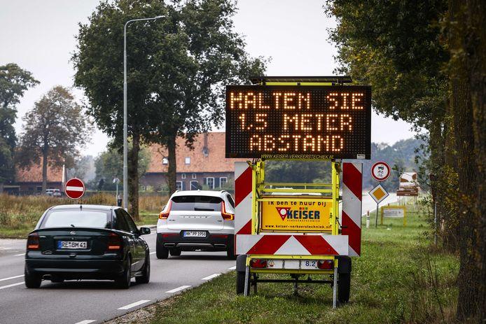Een Informatiebord met oproep om 1,5 meter afstand te houden langs de weg N319 bij de Duitse grens.