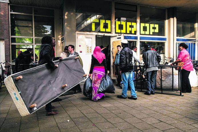 Asielzoekers sjouwen eind mei hun spullen naar binnen in het Toorop gebouw na het vertrek uit de Vluchtkerk.