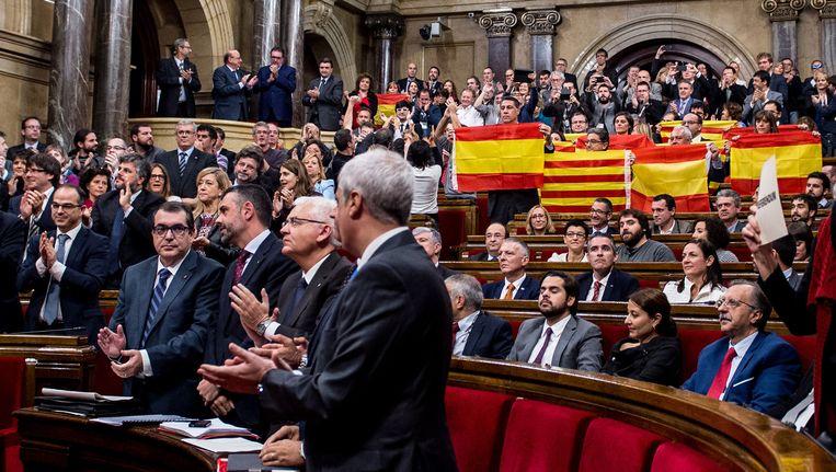 Leden van het Catalaanse parlement hielden maandag Spaanse vlaggen omhoog uit protest tegen de motie. Beeld getty
