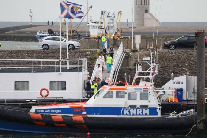 De opvarenden van het motorbootje zijn onderzocht in een ambulance en lopen, in handdoeken gewikkeld, naar het boothuis.