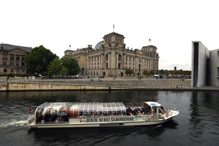 Een rondvaartboot passeert de Reichstag in Berlijn. Voor een trip naar Duitsland moet je aan de grens een negatieve covid- test kunnen tonen die niet ouder is dan 48 uur. Beeld Getty Images