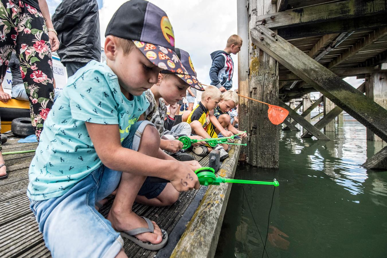 Tim (7) en Rik (4) van Keulen uit Colijnsplaat proberen met hun speciale krabhengels zo veel mogelijk krabben te vangen tijdens het Zeeuws kampioenschap krabben vissen in Colijnsplaat.