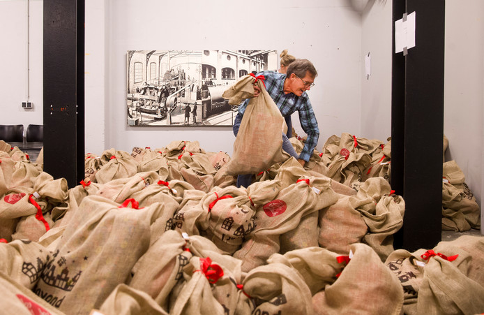 Een vrijwilliger is bezig met het sorteren van zakken vol Sinterklaascadeaus.