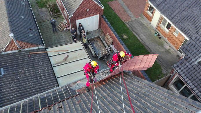 Brandweermannen halen in Zwalm weggewaaide gevelbekleding van een dak.