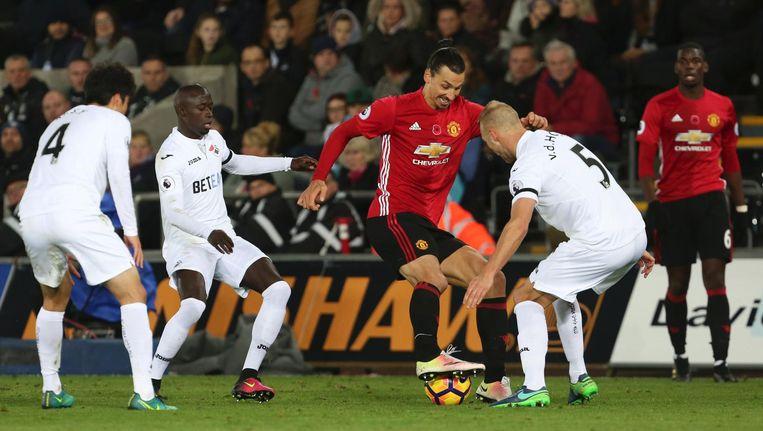 Zlatan Ibrahimovic (C) in duel met Swansea City-verdediger Mike van der Hoorn. Rechts kijkt de duurste speler ooit, Paul Pogba, toe. Beeld anp