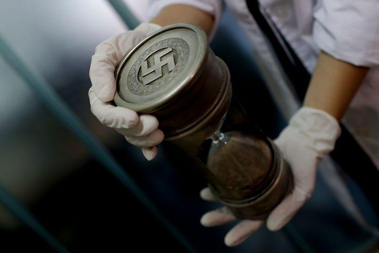 Afgelopen juni werd in Buenos Aires een verzameling nazi-parafernalia ontdekt, zoals deze zandloper, die vermoedelijk ooit hebben toebehoord aan hoge nazi-officieren. Het was de grootste collectie die ooit in Argentinië is gevonden. Beeld AP