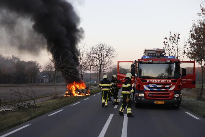 De brandweer van Grave probeert de autobrand op de N321 te blussen.