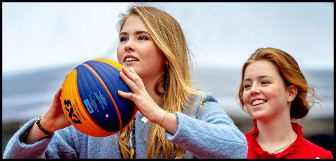 Prinses Amalia steelt de show en gooit lachend een basketbal. Prinses Alexia kijkt toe.