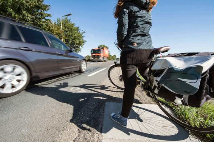 Als je als fietser de Zanddijk over wil steken, rijden de auto's rakelings langs je heen.