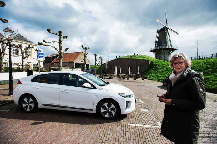 Deelnemer Lies Kersten bij één van de twee deelauto's in Woudrichem.