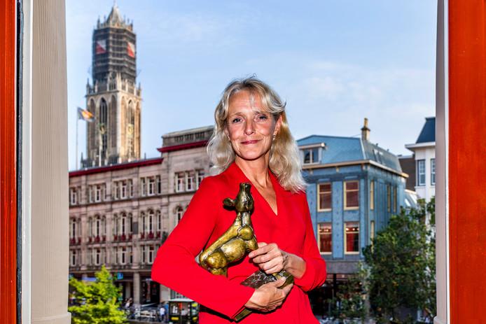 Silvia van der Heiden, de nieuwe algemeen directeur van het Nederlands Film Festival, poserend in de Winkel van Sinkel met een Gouden Kalf.