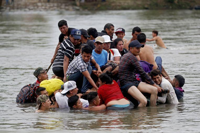 Hondurese migranten steken de rivier tussen Mexico en Guatemala over.