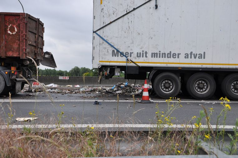 De snelweg wordt opgeruimd nadat de vrachtwagen vol afval kantelde.