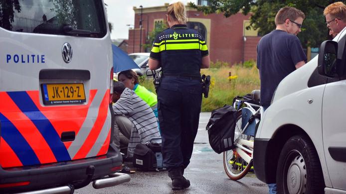 Hulpverleners bekijken het slachtoffer van de aanrijding.