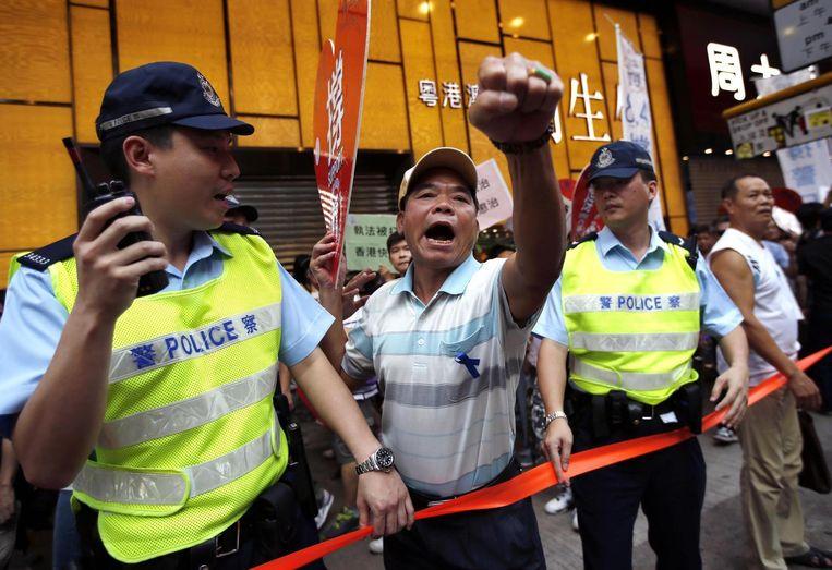 Een betoger wordt tegengehouden door politieagenten tijdens een demonstratie in Hongkong. Beeld reuters