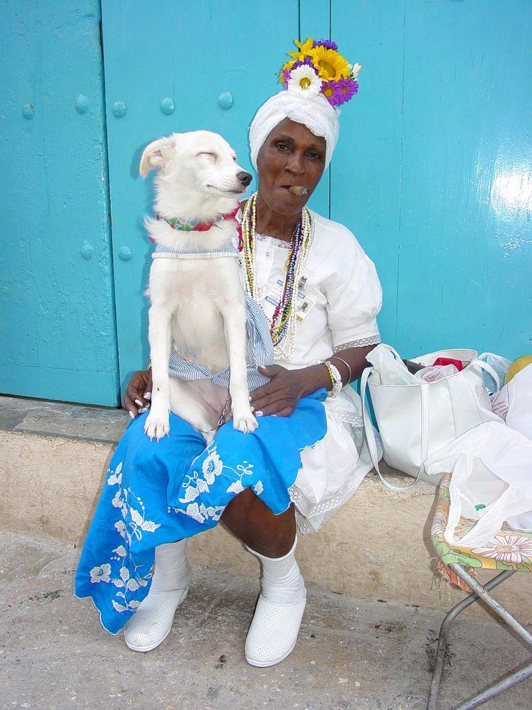 Dame in traditionele uitdossing, met sigaar en hond. Beeld  Adam Jones