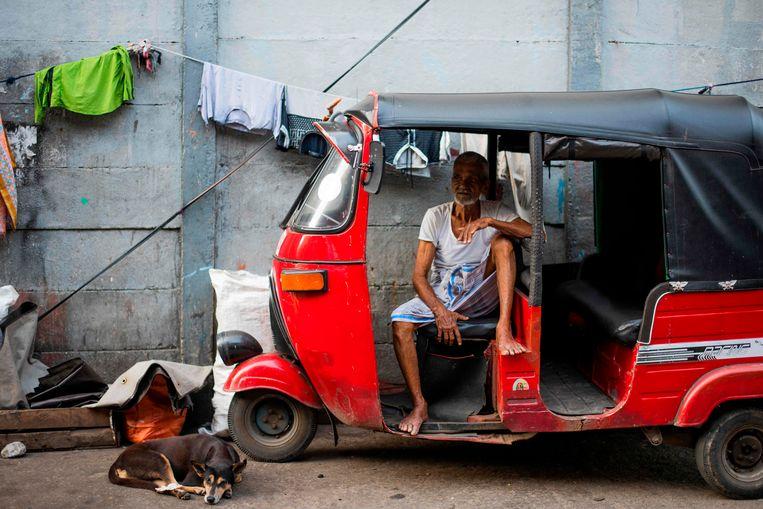Een man in een rickshaw op de straten van Colombo.  Beeld AFP