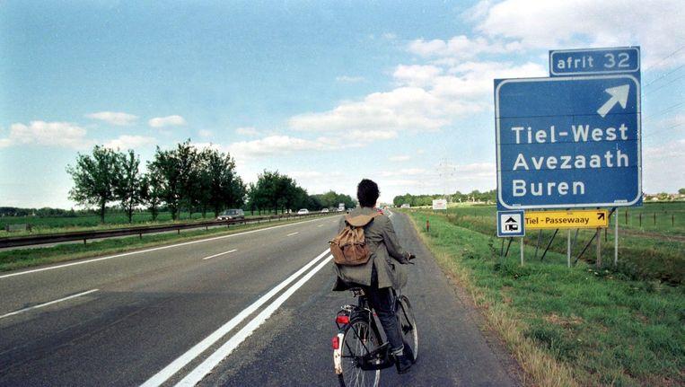 Fietser langs de snelweg Beeld anp