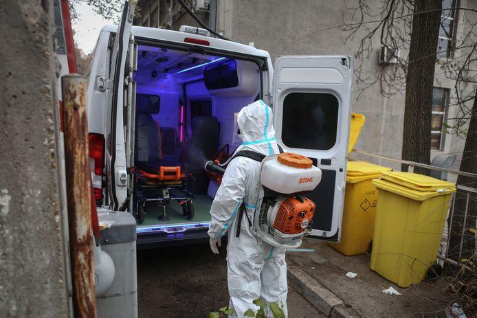 Een medisch hulpverlener desinfecteert een ambulance bij de kliniek voor infectie- en tropische ziekten in Belgrado.