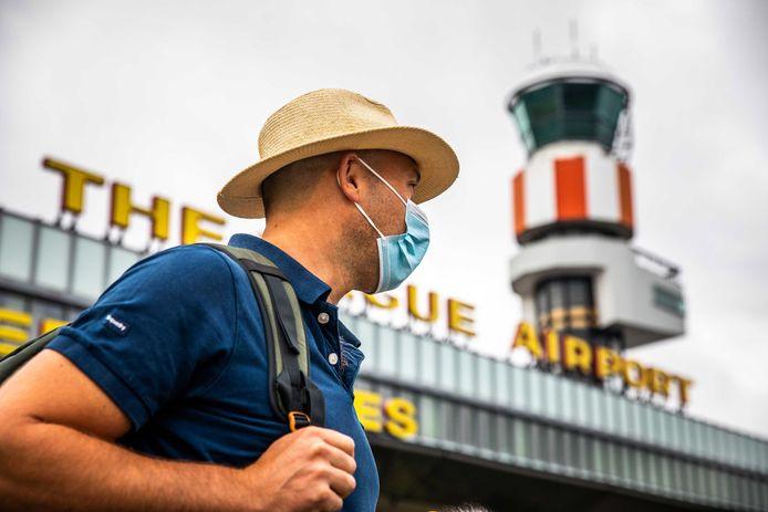Een man met een mondmasker bij Rotterdam The Hague Airport.