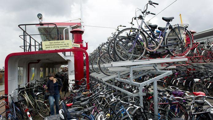 Een vrouw zoekt haar fiets op een oude afgedankte veerpont, die dienst doet als fietsenstalling achter het Centraal Station in Amsterdam.