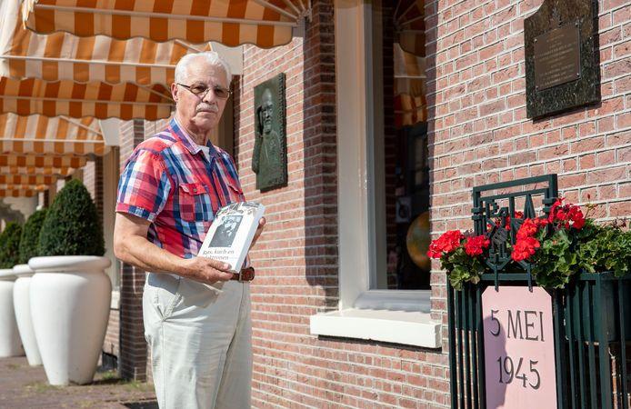 Rob Rijntalder poseert met zijn boek bij Hotel de Wereld in Wageningen.