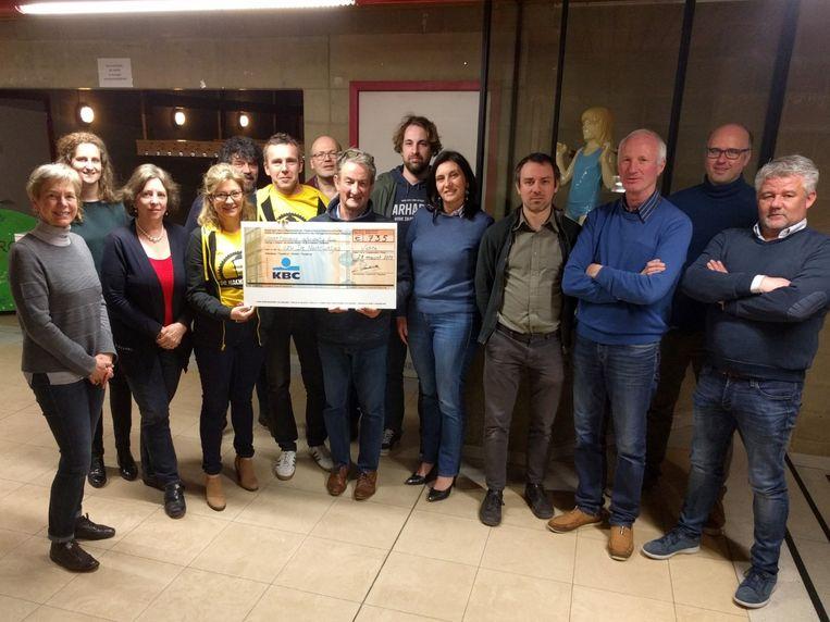 Karel Demeulemeester overhandigde de cheque van Isabelle Parmentier en Steven Verhaeghe van De Nachtlichtjes. Ook op de foto: alle bestuursleden van de Vichtse Dorpsraad.