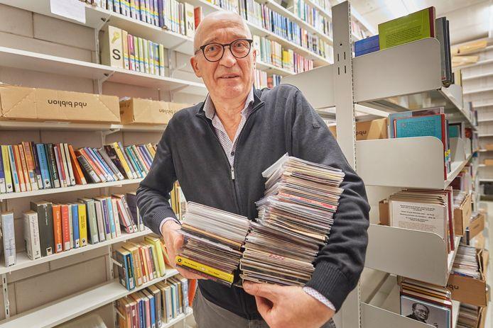 Hans van Duijnhoven van de bibliotheek Oss met stapels te verkopen cd's.