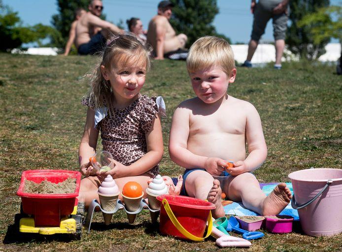 Het is druk bij de Haarrijnseplas met zwemmers en zonaanbidders. Tessa en vriendje Huub spelen samen.