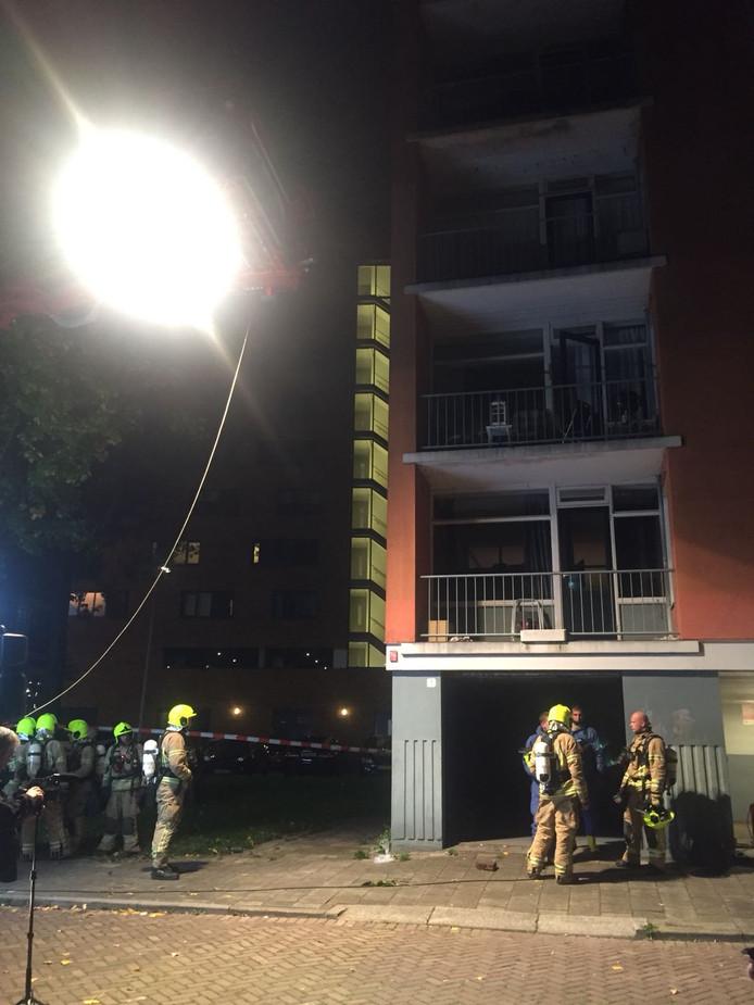 Bij deze flat wordt de lucht geroken. Een hoogwerker met lamp geeft extra zicht bij het onderzoek.