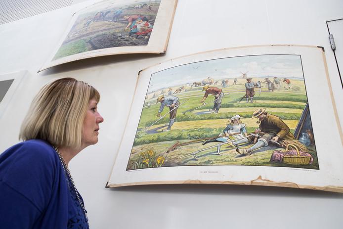 De expositie over oude  schoolartikelen is te zien in het gemeentehuis van Wijhe.  Riki Klein Woolthuis bekijkt een oude schoolplaat