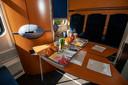 In de Nightjet krijgen reizigers 's ochtends een ontbijtje geserveerd. Hier de zitcoupé met normaliter plek voor zes mensen en door corona vier. De stoelen zijn tot slaapplekkem om te bouwen.