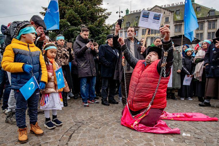 Een geboeide demonstrant tijdens het protest solidair met de Oeigoeren op de Dam in Amsterdam. Beeld SOPA Images / LightRocket via Getty