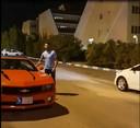 De rode, gehuurde sportwagen heeft ook een nummerbord van het eiland Kish.