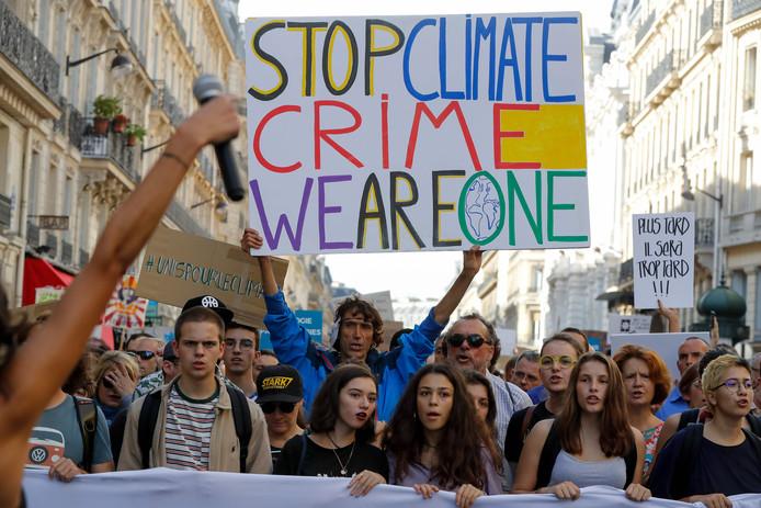 """De Franse activist Jean-Baptiste Redde, aka Voltuan (m) loopt met een protestbord met de tekst: """"Stop de klimaatmisdaad, wij zijn één"""" tijdens de Mars tegen klimaatverandering in Parijs."""