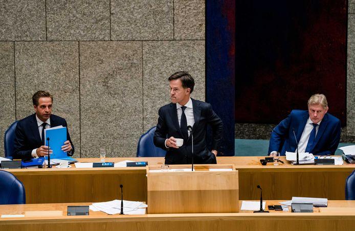 Premier Rutte met ministers Hugo de Jonge (Volksgezondheid) links en Martin van Rijn (Medische Zorg) tijdens het Tweede Kamerdebat over de ontwikkelingen rondom het coronavirus.