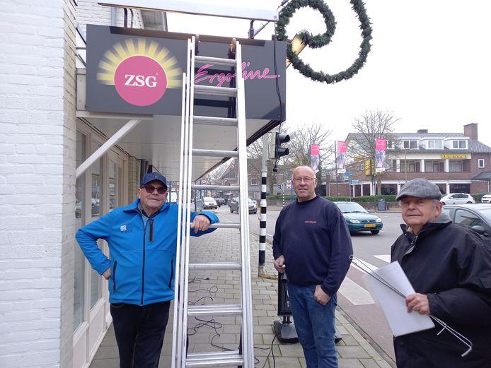 Vrijwilligers van fanfare Wilhelmina versieren de winkels van Groesbeek.