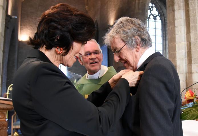 Pauselijke onderscheiding voor Anton de Kort. Zijn echtgenote speldt de onderscheiding op onder toezicht van pastoor Wiel Wiertz.