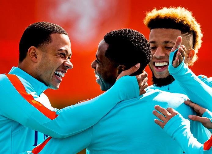 De sfeer zit er weer goed in bij Oranje: Memphis Depay heeft plezier in het oortje tikken met Quincy Promes en Tonny Vilhena.