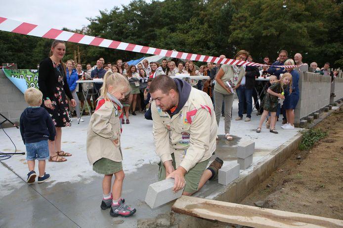 Het jongste en het oudste lid van de scouts van Averbode leggen samen de eerste steen.