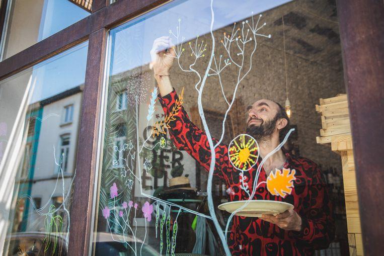 Marc-Aurèle Versini maakt een tekening op een raam van Akker en Ambacht in de Brugse Poort.