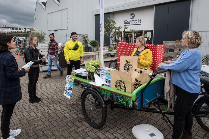 Brenda Leenders (gele jas) met de mobiele vrijwilligerswinkel in Tiel
