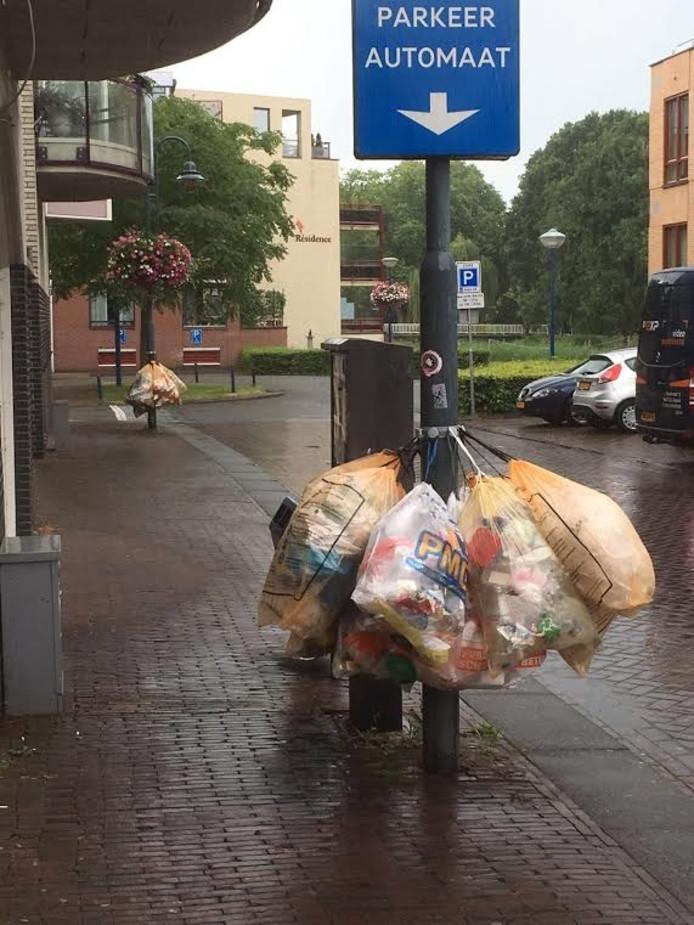 Plastic afval gehangen aan palen in Veghel.