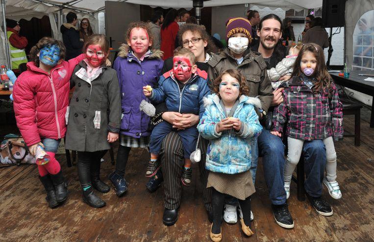 Freedom met mondmasker (midden) met zusje Hope (blauw gezichtje, links), zijn papa en mama en enkele vriendjes.