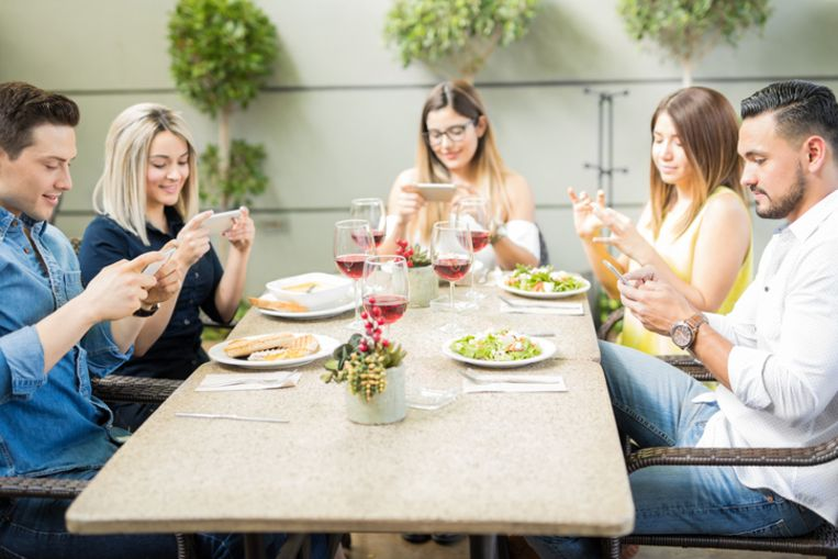 Group of five good looking friends using their smartphones to take photos of their food in a restaurant