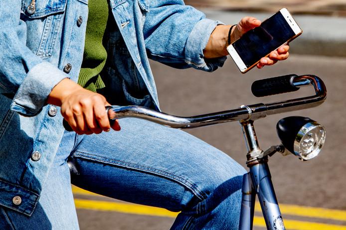 Een jongere appt op de fiets in Rotterdam.
