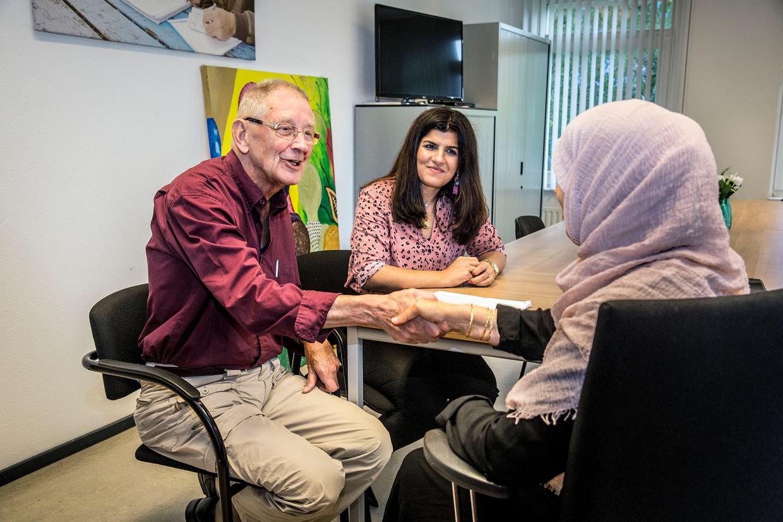 Vrijwilligers Leen den Boer en Fermesk Saleh Kidhir op het kantoor van Vluchtelingenwerk in Vlaardingen.