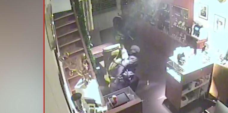 Eén man graait de achterste rekken leeg, terwijl een tweede de trap afstormt.